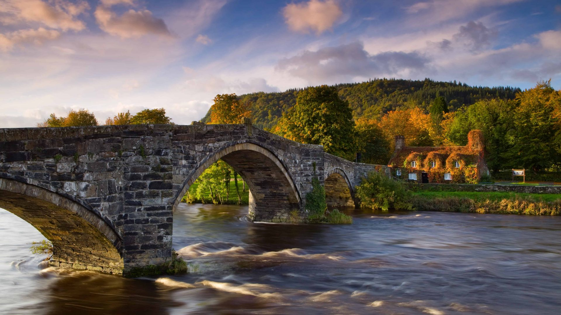 Tu Hwnt I'r Bont, a former courthouse, and the 17th century Pont Fawr stone bridge on the river Conwy. Sunset, dusk.