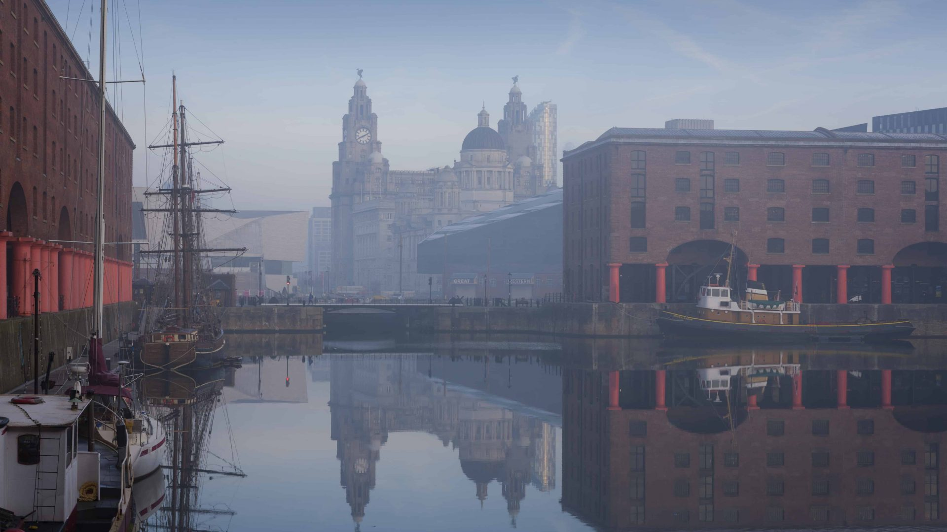 Maritime Albert Dock on Liverpool waterfront with the Three Graces historic buildings. The Liverpool world heritage site. Port of Liverpool building, the Cunard Building and the Liver building. A historic ship moored. Mist rising from the water.